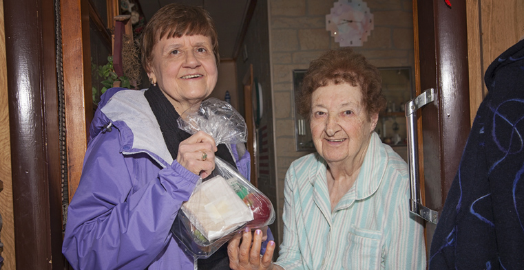 Elaine Mykolayko, left, delivers a meal to Olga Kosick. Mykolayko, a Diakon volunteer, was recently recognized as citizen-of-the-year in Frackville, Pennsylvania.