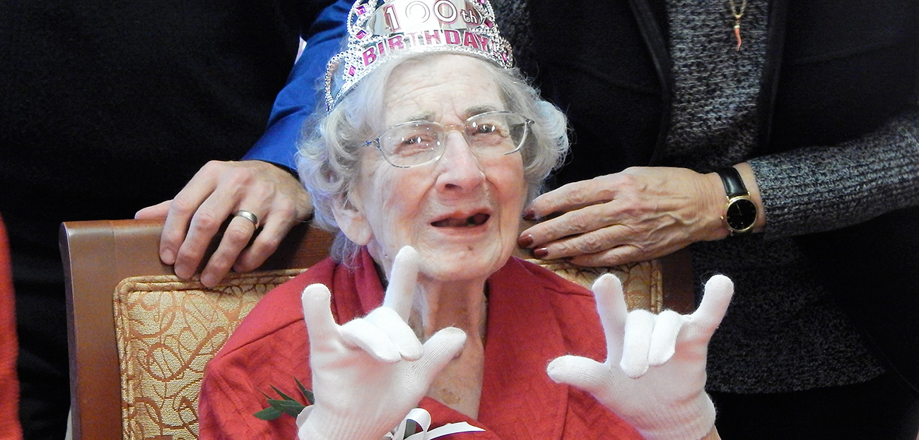 "Mrs. Harriet MacDonald displays the signs for ""I love you"" during her 100th birthday party"