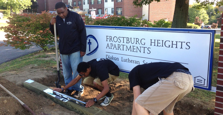 Keith Mutinda, left, and other Flight participants work on landscaping the sign at the entrance to Diakon's Frostburg Heights Apartments in western Maryland.
