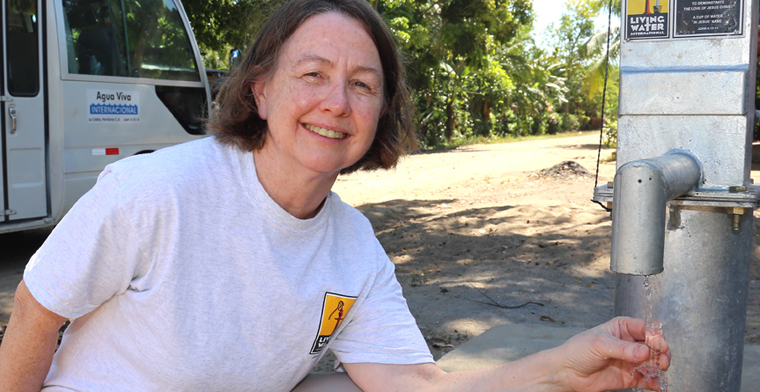 The Rev. Dianne Kareha, a Diakon chaplain, poses at the well she and a mission group helped to dig in Honduras. Her trip was assisted through Diakon's Love of Our Neighbor Fund.