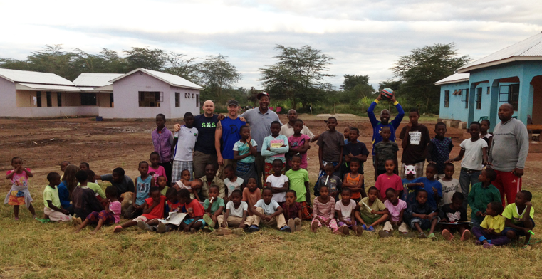 Rob Kivlan, Corey Carothers, and Anthony Stukes, left to right in center, pose for a group photograph with children and staff members from the Majengo Orphanage in Tanzania.