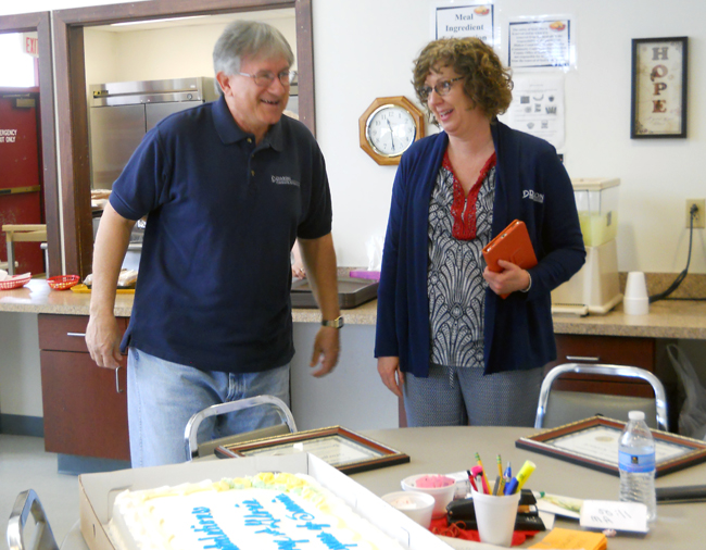 George Koback shares an enjoyable moment with Tracy Miller, Meals on Wheels coordinator, right, before cake-cutting time at the recent celebration.