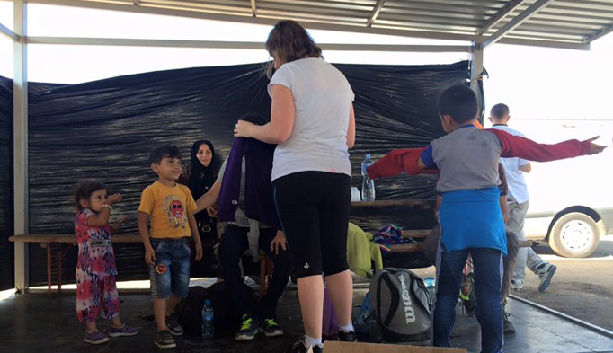 Heidi Storey, back to camera, offers a sweater to a Syrian child on a recent trip to Macedonia to aid refugee children.