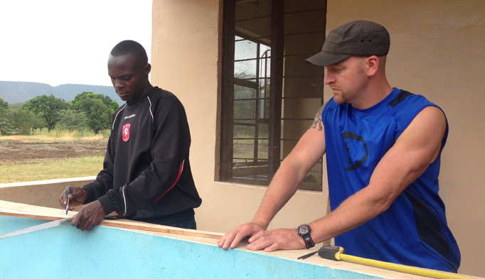Corey Carothers, right, works with a staff member of the Majengo Orphanage in Tanzania on repairs to one of the buildings.