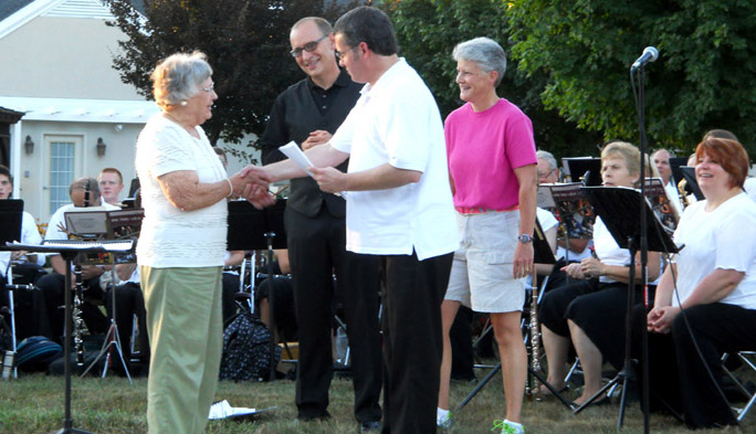 In this photograph that appeared in the August 2013 eDiakonnect, Janet Clark, left, receives the commission for the march, given by an anonymous donor in her honor, from composer Dr. Michael A. Harcrow, second from left. Dr. William Stowman, conductor, and Jan Bigelow, Cumberland Crossings executive director, look on.