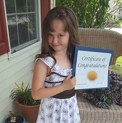 Adopted or fostered child proudly holding certificate of achievement.